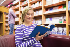 Young woman reading book. Young women reading book in library Stock Images