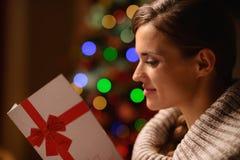 Young woman reading Christmas postcard Royalty Free Stock Photos