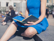 Young woman reading in the city Stock Images