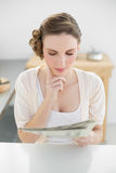 Young woman reading concentrated newspaper sitting in her kitchen Stock Image