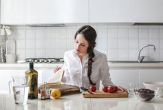 Young woman reading a cook book. Young beautiful woman reading a cook book and learing how to cook Stock Images