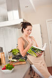 Young woman reading cookbook in the kitchen Stock Photo