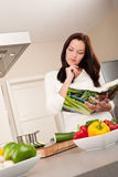 Young woman reading cookbook in the kitchen Stock Photos