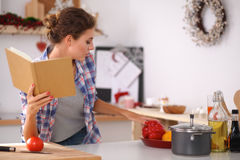 Young woman reading cookbook in the kitchen, Royalty Free Stock Photos