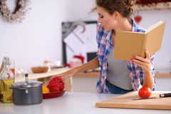Young woman reading cookbook in the kitchen Royalty Free Stock Photo