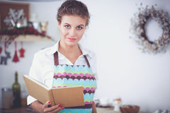 Young woman reading cookbook in the kitchen, looking for recipe Stock Photography