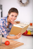 Young woman reading cookbook in the kitchen, Stock Photos