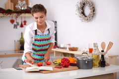 Young woman reading cookbook in the kitchen, Stock Photography