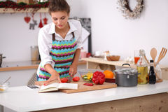 Young woman reading cookbook in the kitchen, Royalty Free Stock Image
