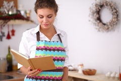 Young woman reading cookbook in the kitchen, Royalty Free Stock Photography