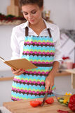 Young woman reading cookbook in the kitchen, Royalty Free Stock Images