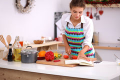 Young woman reading cookbook in the kitchen Royalty Free Stock Images