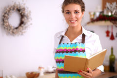 Young woman reading cookbook in the kitchen Royalty Free Stock Image