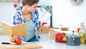 Young woman reading cookbook in the kitchen, looking for recipe.  Stock Photos