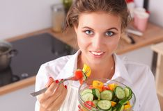 Young woman reading cookbook in the kitchen, looking for recipe.  Royalty Free Stock Photography