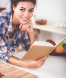 Young woman reading cookbook in the kitchen, looking for recipe.  Stock Photography