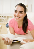 Young woman reading on couch Stock Images