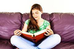 Young woman reading cross-legged on a sofa Royalty Free Stock Images