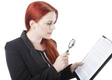 Young Woman Reading Document with Magnifying Glass Royalty Free Stock Image