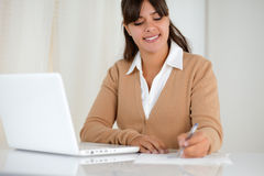 Young woman reading documents and using laptop Royalty Free Stock Photo