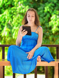 Young woman reading e-book. Outdoor portrait Stock Photos