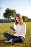 Young woman reading e-book outdoor Royalty Free Stock Photo