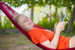 Young woman reading on electronic tablet reader relaxing in hamm Royalty Free Stock Photo