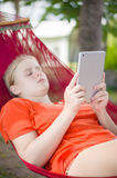 Young woman reading on electronic tablet reader relaxing in hamm Stock Photography