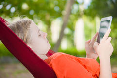 Young woman reading on electronic tablet reader relaxing in hamm Stock Images