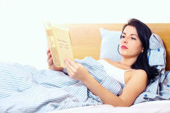 Young woman reading fascinating novel in bed Royalty Free Stock Photos