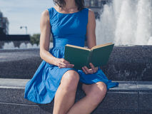 Young woman reading by fountain in the city Stock Photos