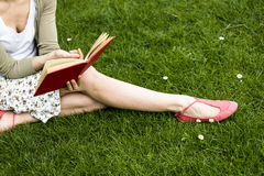Young woman reading on the grass. Young woman sitting on the green grass reading Royalty Free Stock Photos