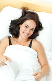 Young woman reading in her bed Stock Photo