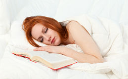 Young woman reading in her bed Stock Photography