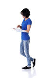 Young woman reading her notebook for school. Royalty Free Stock Images