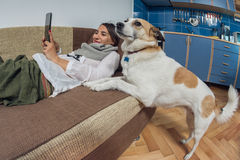 Young woman reading from her tablet and her dog Royalty Free Stock Photography