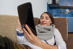 Young woman reading from her tablet Stock Images