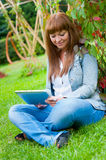 Young Woman Reading In Tablet Pc Royalty Free Stock Images