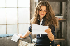 Young woman reading letter in loft apartment. Young woman reading letter in modern loft apartment Royalty Free Stock Image