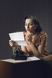 Woman reading a letter sitting on armchair Royalty Free Stock Photo