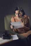 Woman reading a letter with worried expression Royalty Free Stock Photo