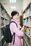Young woman reading in library. A young woman reading in the library Royalty Free Stock Photos