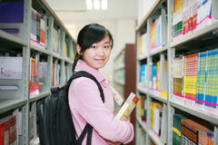 Young woman reading in library stock photo