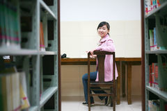 Young woman reading in library Royalty Free Stock Images