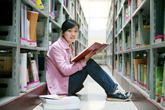 Young woman reading in library Royalty Free Stock Photo