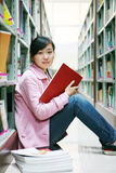 Young woman reading in library. A young woman reading in the library Royalty Free Stock Image