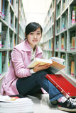 Young woman reading in library Stock Image