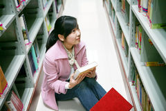 Young woman reading in library. A young woman reading in the library Stock Photos