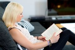 Young woman is reading in the living room Stock Images