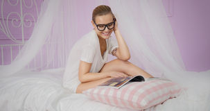 Young woman reading magazine. stock images